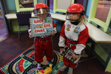 Nicholas Fecht and Natalie Deering model racing suits that will be available for dress up at the Wood County Library in Bowling Green as part of its summer reading activities.