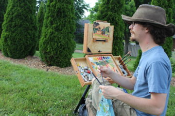 Aaron Pickens paints in the park.