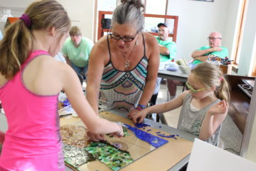 Gail Christofferson works with Reagan Otley, left, and Maggie Otley, right, on a panel for the glass mosaic at Art in the Park in June.