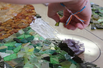 Reagan Otley places a piece of glass onto the mosaic panel.