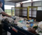 Jamie Babcock, of Community Employment Services, sorts through recyclables mixed with trash.