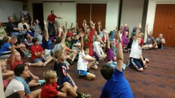 Students raise hands to answer U.S. Constitution questions.