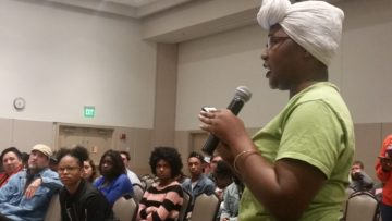 Naje Crawford speaks during town hall